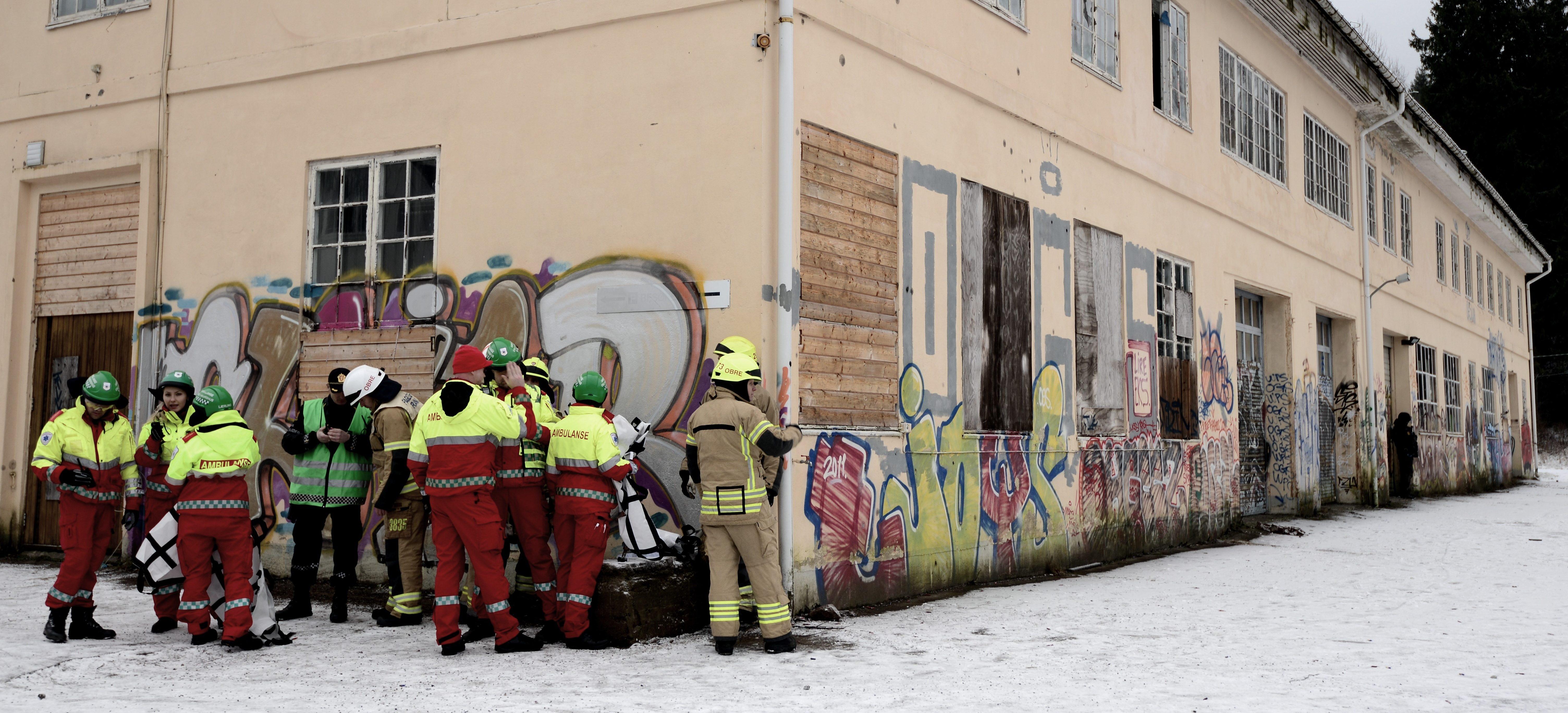 Brannmenn og ambulansefolk ventar bak eit hushjørne (illustrasjonsfoto)