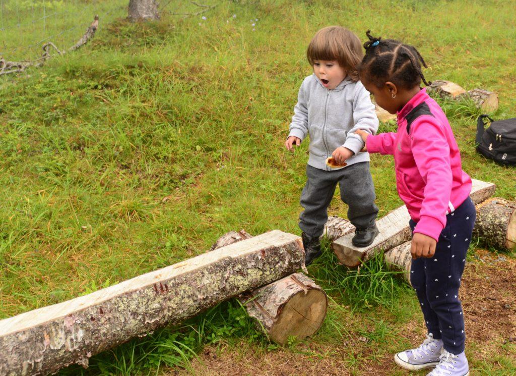 Sabrina hjelper ein liten gut å balansere på ein stokk.